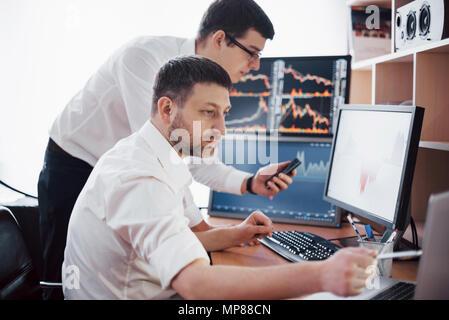 Les stocks commerciaux d'affaires en ligne. Les courtiers en regardant des graphiques, des index et des chiffres sur plusieurs écrans d'ordinateur. Collègues de discussion dans traders bureau. La réussite de l'entreprise concept Banque D'Images