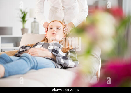 Le soulagement du stress et relaxation concept - young woman lying on couch au bureau du médecin ayant head massage Banque D'Images