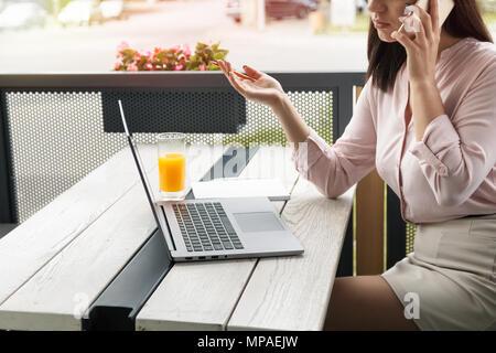 Jeune femme parlant d'affaires sur le téléphone et de tenir un crayon en gesticulant, ordinateur portable et de jus sur 24. Banque D'Images