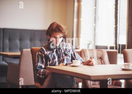 Homme heureux propriétaire de café confortable se réjouissent de propre succès alors qu'il était assis avec touch pad à table à manger, male holding digital tablet et pense à quelque chose de bien pendant le déjeuner in coffee shop Banque D'Images