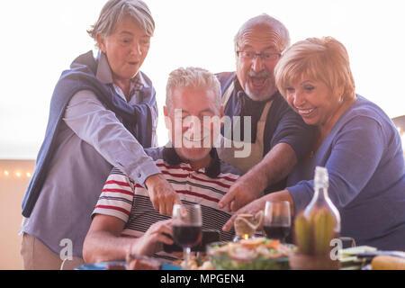Deux beaux couples doing photo avec téléphone mobile pendant le dîner sur le toit-terrasse en plein air. vacances pour les retraités de la vie heureux concept Banque D'Images
