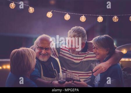 L'accent sur l'homme. groupe de personnes adultes âgés de faire partie de nuit sur le toit de la maison. Tout le monde hug sourire et rire ensemble et pour une activité agréable Banque D'Images