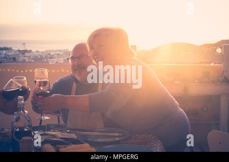 Groupe d'amis adultes âgés de hauts en train de dîner et faisant partie agréable moment dans le toit-terrasse piscine avec du vin et de l'alimentation. s'amuser pendant la s Banque D'Images