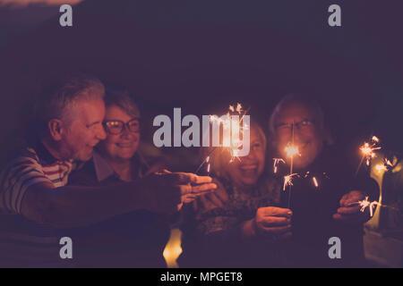 Temps de célébration pour la fête de fin d'année ou pour un groupe d'amis senior avec le feu d'étincelles. averybody s'amuser ensemble dans la nuit en souriant et laughin Banque D'Images