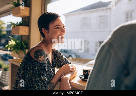 Attractive young woman smiling et parler avec son homme au restaurant. Femme ayant un bon moment avec son petit ami dans un café. Banque D'Images