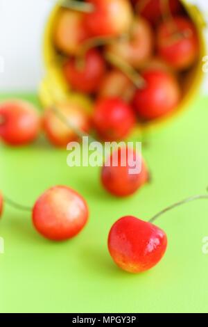 Les cerises dans un seau sur la vieille table en bois - les fruits d'été Banque D'Images