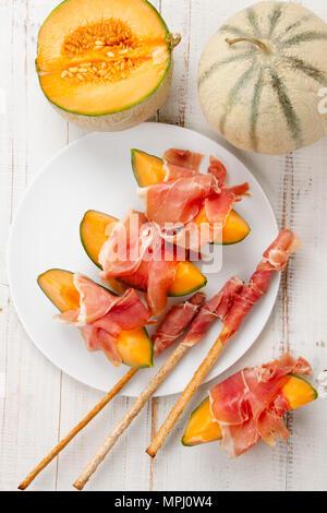 Melon cantaloup avec du jambon, un apéritif italien et espagnol traditionnel servi avec aliments complets grissini Banque D'Images
