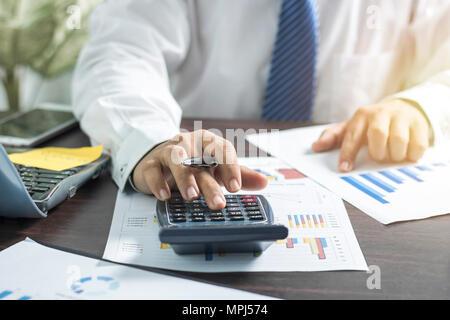 Businessman pushing et agissant sur la calculatrice et à la recherche d'affaires sur papier, sur la table de travail concept finance Banque D'Images