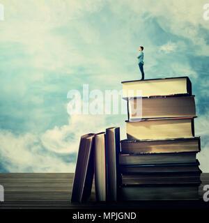 Jeune étudiant, debout sur le sommet d'un énorme tas de livres à la mesure à l'horizon. Idée et concept de savoirs. Banque D'Images