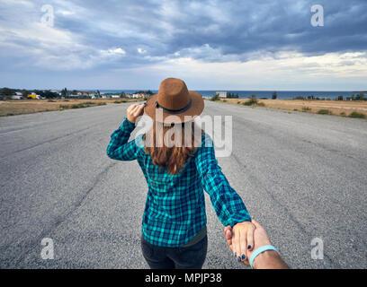 Heureux couple in checked shirt holding par les mains et marcher sur la large route asphaltée avec lac et fond de ciel nuageux Banque D'Images
