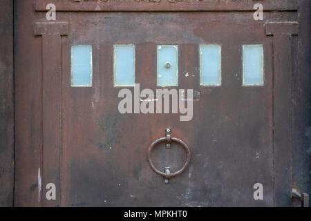 Fond métallique porte métallique brun rouille avec des rectangles de verre bleu et une lourde bague dans le milieu. Banque D'Images