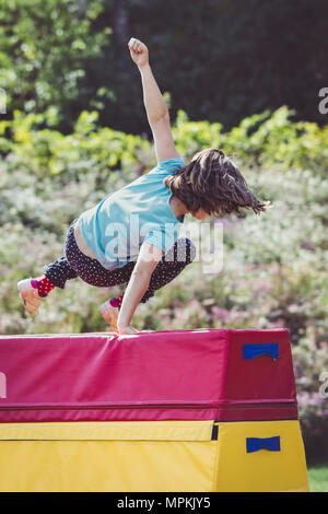Petite fille pratique (pratique) en dehors de la gymnastique sur cheval de saut Banque D'Images