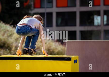 Petite fille pratique (pratique) en dehors de la gymnastique Parkour sur cheval de saut Banque D'Images