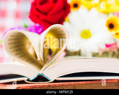 Livre ouvert et pages qui forment le coeur forme avec fleur en fond. L'amour et la Saint-Valentin concept. Banque D'Images
