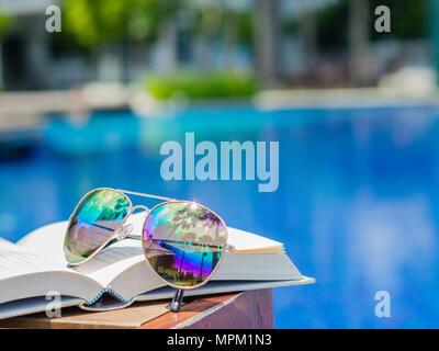 Lunettes de livre ouvert sur le côté de la piscine. Plage, vacances, été travel concept Banque D'Images