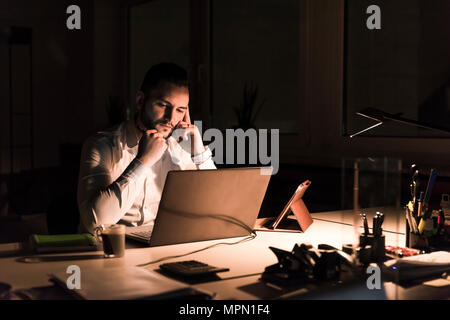 Pensive businessman working on laptop in office at night Banque D'Images