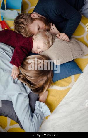 Paliers de repos en famille ensemble sur le sol après la lecture