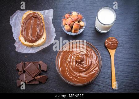 Tranche de pain avec la crème au chocolat et noisettes propagation sur le tableau noir. Servant un délicieux petit-déjeuner gratuit. Banque D'Images