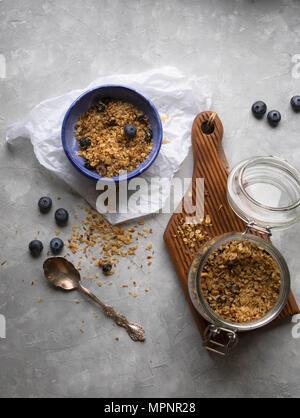 Granola fait maison dans un bocal en verre et dans un bol avec des bleuets frais sur fond gris