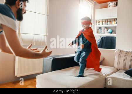 Père jouant avec son petit garçon habillé en super héros à la maison Banque D'Images