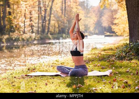 Mid adult woman in forest pratiquant le yoga, la méditation Banque D'Images