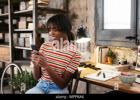 Souriante jeune femme assise en face de bureau dans un loft looking at cell phone Banque D'Images