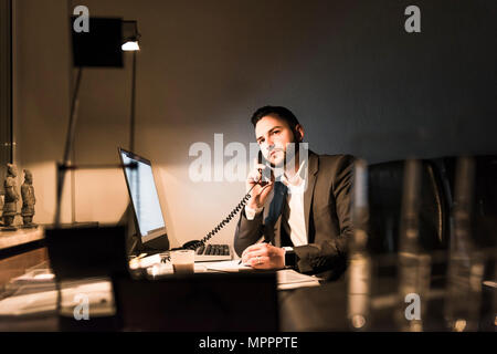 Businessman on the phone in office at night Banque D'Images