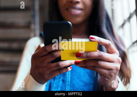Woman's hands holding cell phone et wifi keycard, close-up Banque D'Images