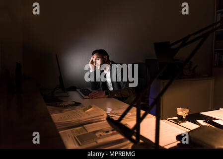 Pensive young businessman sitting at desk in office at night Banque D'Images