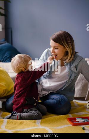 Mère jouant avec son bébé, qui nourrit sa