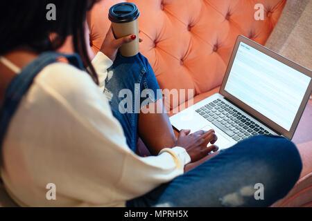Jeune femme assise sur le canapé avec un café d'aller à l'aide d'ordinateur portable Banque D'Images