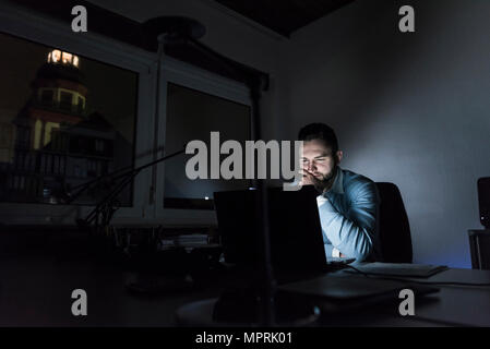 Businessman working on laptop in office at night Banque D'Images