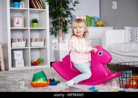 Portrait of smiling little girl sitting sur cheval à bascule rose dans la salle de séjour Banque D'Images