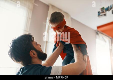 Père jouant avec son petit garçon habillé en super héros Banque D'Images