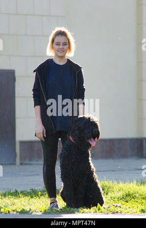 Les jeunes peuplements mort a avec son chien sur l'herbe verte, sur l'arrière-plan de l'édifice dans le parc Banque D'Images