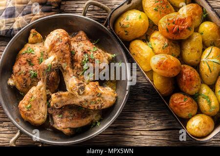 Cuisses de poulet rôti avec des pommes de terre au cumin et herbes poivre haut de vue. Banque D'Images