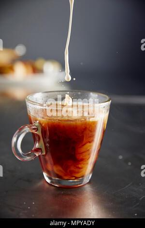 Close-up de verser le lait dans la tasse de café sur la table Banque D'Images