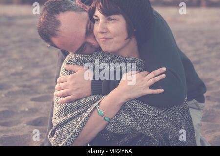 Mignon l'homme et la femme d'âge moyen s'amusant dans l'amour à la plage. activité de loisirs de plein air et gros câlin pour l'amour et la scène concept romantique homme embra Banque D'Images