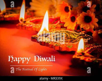 L'argile colorée lampes diya éclairé avec des fleurs pour la Diwali festival hindou. Banque D'Images