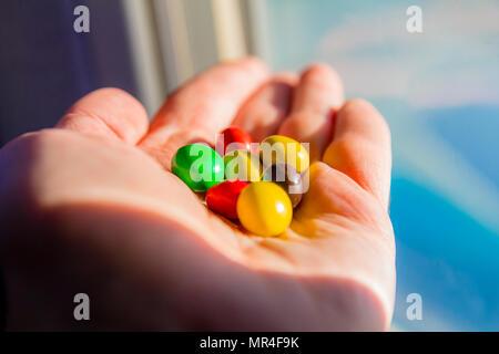 Tenir la main de l'homme chocolat bonbons colorés boutons. Banque D'Images