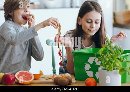 Les enfants jouent avec un apple peau lors de la ségrégation des déchets dans la cuisine Banque D'Images