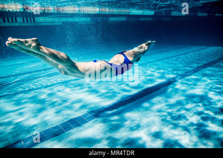 Photo sous-marine de jeune nageuse exercising in swimming pool Banque D'Images