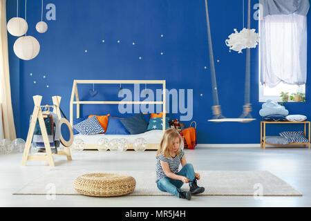 Girl chambre avec mur bleu, swing, porte manteau et double