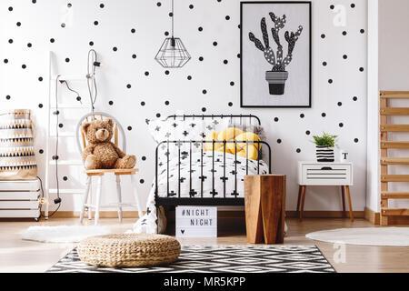 Ours en peluche sur une chaise à côté du lit avec oreiller jaune dans la chambre des enfants avec tapis pouf sur scandi Banque D'Images