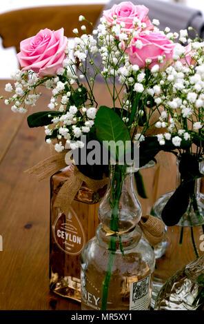 Simples arrangements de roses roses et gypsophile blanc en bouteilles de verre préparé comme décorations de table de réception de mariage. Banque D'Images