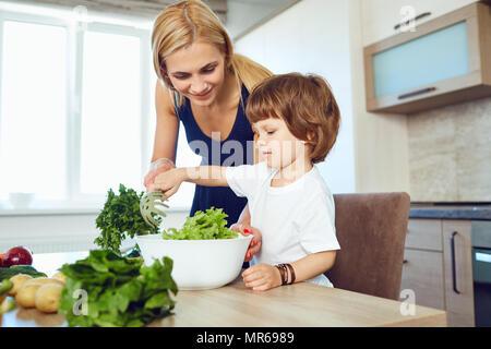 Maman et son enfant sont la préparation des aliments dans la cuisine. Banque D'Images