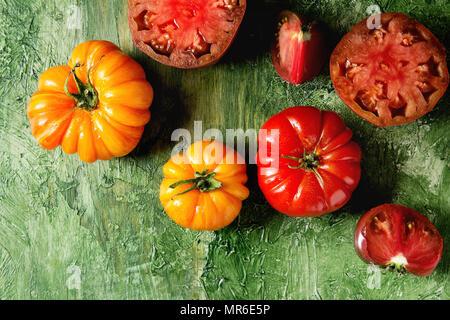 Variété de tomates biologiques rouge et jaune pour la salade verte sur fond de texture. Vue de dessus, copiez l'espace. Banque D'Images