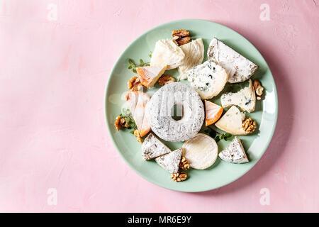 Plateau de fromages assortiment de fromages français servi avec des noix sur une plaque en céramique turquoise rose sur fond pastel. Vue de dessus, de l'espace.