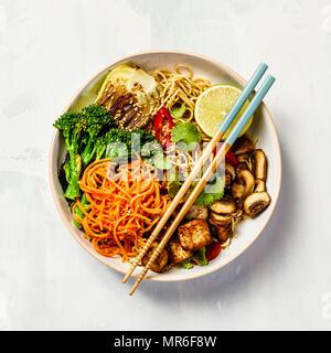 Nouilles végétarien avec tofu, le brocoli, les champignons, la carotte, le bok choy sur table en pierre blanche. Haut de la vue, télévision lay, copyspace Banque D'Images
