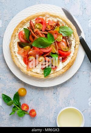 Tartelette ronde rempli de tomates cerise, la pancetta, le fromage feta et le basilic sur une plaque avec un couteau. Banque D'Images